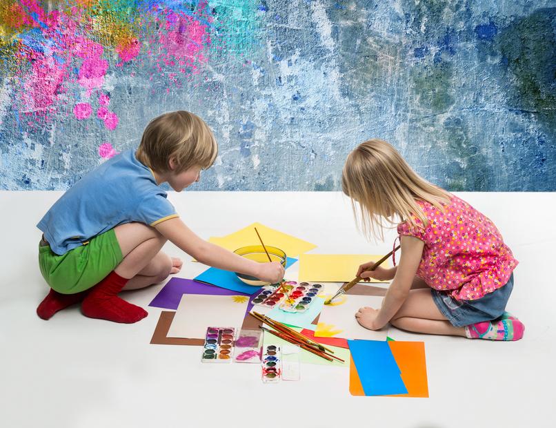 Children draw of paints on the floor